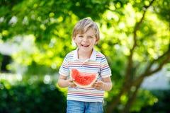 Little preschool kid boy eating watermelon in summer Stock Images