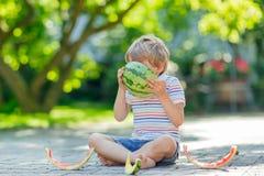 Little preschool kid boy eating watermelon in summer Stock Image
