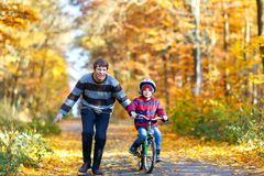Little kid boy and his father in autumn park with a bicycle. Dad teaching his son biking Stock Photos