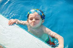 Little preschool kid boy making swim competition sport. Kid with swimming goggles reaching edge of the pool . Child stock photos
