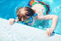 Little preschool kid boy making swim competition sport. Kid with swimming goggles reaching edge of the pool . Child royalty free stock images