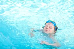 Little preschool kid boy making swim competition sport. Kid with swimming goggles reaching edge of the pool . Child royalty free stock photo