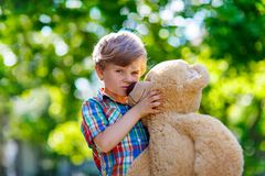 Little kid boy playing with big plush bear, outdoors. Stock Photo