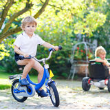 Little preschool kid boy riding with bicycle in summer Stock Photography