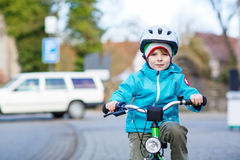 Little preschool kid boy riding with his first green bike Royalty Free Stock Image