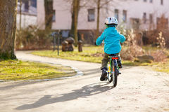 Little preschool kid boy riding with his first green bike Royalty Free Stock Photography