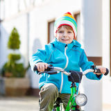 Little preschool kid boy riding with his first green bike Stock Image