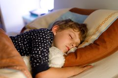Little preschool kid boy sleeping in bed with colorful lamp. stock images