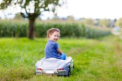 Little preschool kid girl sitting on old big toy car and having fun on sunny summer day Royalty Free Stock Images