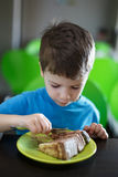 Little preschooler boy eating cake in confectionery Royalty Free Stock Photos
