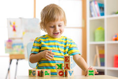 Little preschooler child boy playing with toy cubes and memorizing letters. Early education concept Royalty Free Stock Images