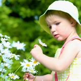Little preschooler girl playing in flower garden Royalty Free Stock Photos
