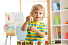 Little preschooler kid boy playing with toy cubes and memorizing letters. Early education and preschool concept Stock Photos