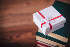 Little present box on top  of books. The gift of learning concept - little present box on top of a pile of books Royalty Free Stock Images
