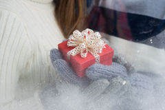 Little present. Close-up of a little giftbox in hands in mittens Royalty Free Stock Images
