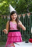 Little preteen pretty girl with thick brown hair. In birthday cone hat close up party photo on summer green ourdoor background Stock Photo