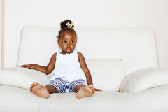 Little pretty african american girl sitting in white chair weari Royalty Free Stock Photos