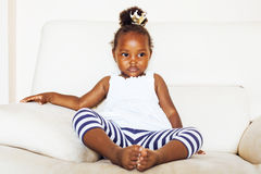 Little pretty african american girl sitting in white chair weari Royalty Free Stock Images