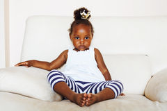 Little pretty african american girl sitting in white chair weari Royalty Free Stock Photography