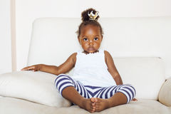 Little pretty african american girl sitting in white chair wearing toy crown on head like princess or queen, lifestyle Royalty Free Stock Photo