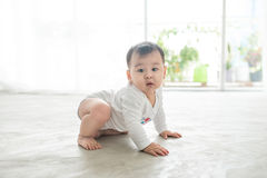 Little pretty baby girl crawling on the floor at home Stock Photos