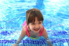 Little pretty beautiful girl swimming in the pool child. Kid baby infant youngster aquatics water sport active game joy merriment mirth gaiety hilarity rejoicing Stock Image