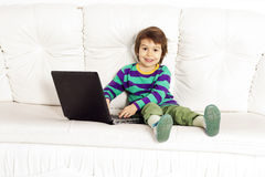 Little pretty boy on the sofa with notebook Royalty Free Stock Photography