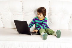Little pretty boy on the sofa with notebook Royalty Free Stock Images
