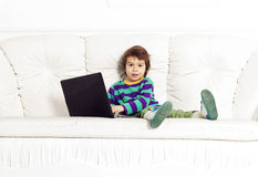 Little pretty boy on the sofa with notebook Stock Image