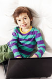 Little pretty boy on the sofa with notebook Royalty Free Stock Photos