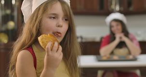 Little pretty Caucasian girl eating bun at the kitchen at home. Cute child enjoying tasty bakery as her mother sitting stock video