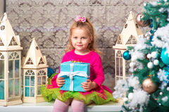 Little pretty curly blonde smiling girl sitting on the windowsill nearly Christmas tree Stock Image