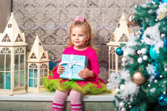 Little pretty curly blonde smiling girl sitting on the windowsill nearly Christmas tree Royalty Free Stock Photo