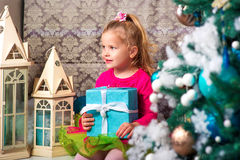 Little pretty curly blonde smiling girl sitting on the windowsill nearly Christmas tree Stock Photos