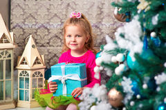 Little pretty curly blonde smiling girl sitting on the windowsill nearly Christmas tree Royalty Free Stock Images