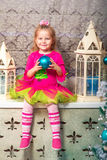 Little pretty curly blonde smiling girl sitting on the windowsill nearly Christmas tree Royalty Free Stock Photography