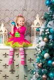 Little pretty curly blonde smiling girl sitting on the windowsill nearly Christmas tree Stock Photography