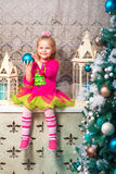 Little pretty curly blonde smiling girl sitting on the windowsill nearly Christmas tree Stock Images