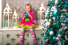Little pretty curly blonde smiling girl sitting on the windowsill nearly Christmas tree Royalty Free Stock Image