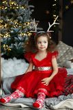 Little pretty curly smiling girl sitting nearly Christmas tree with Christmas decorations and presents. Child in red dress and soc royalty free stock image