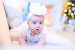 Little pretty female baby with blue eyes lying on sofa and wearing white clothes. royalty free stock image