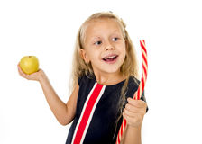 Little pretty female child choosing dessert holding unhealthy but tasty red candy licorice and apple fruit Royalty Free Stock Photos