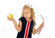 Little pretty female child choosing dessert holding unhealthy but tasty red candy licorice and apple fruit Stock Photography