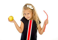 Little pretty female child choosing dessert holding unhealthy but tasty red candy licorice and apple fruit Royalty Free Stock Photography