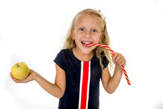 Little pretty female child choosing dessert holding unhealthy but tasty red candy licorice and apple fruit Royalty Free Stock Photo