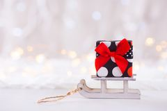Little pretty gift box on toy white sled on light bokeh backgrou Royalty Free Stock Photography