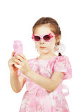 Little pretty girl in beautiful pink dress with toy mobile Stock Images