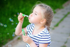 A little pretty girl blowing soap bubbles. Outdoors Stock Photos