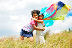 A little pretty girl and boy. With scarf above head on medow Royalty Free Stock Image