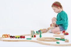 Little pretty girl builds railway from wooden parts Royalty Free Stock Images